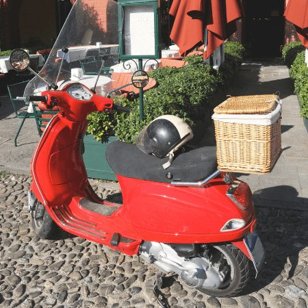 Red scooter with a wicker basket on the back rack