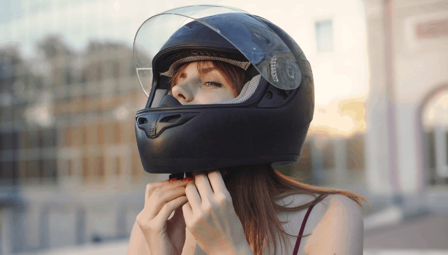 Woman with long hair putting on motorcycle helmet