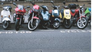Variety of motorcycles, mopeds and scooters in motorcycle parking area