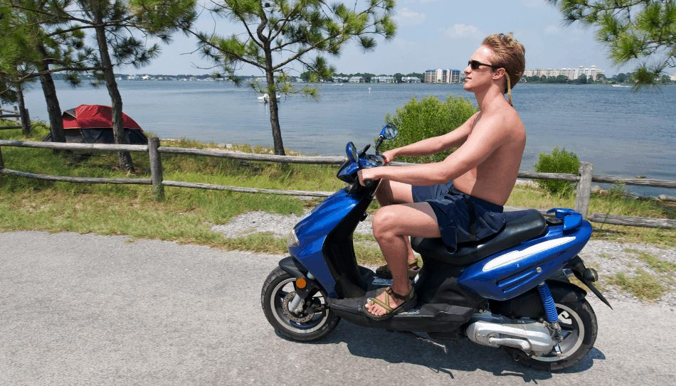 Man riding a scooter on vacation near a lake