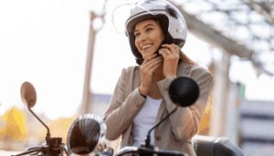 woman putting on a motorcycle helmet