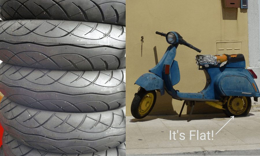 Image of scooter with a flat tire and a stack of scooter tires