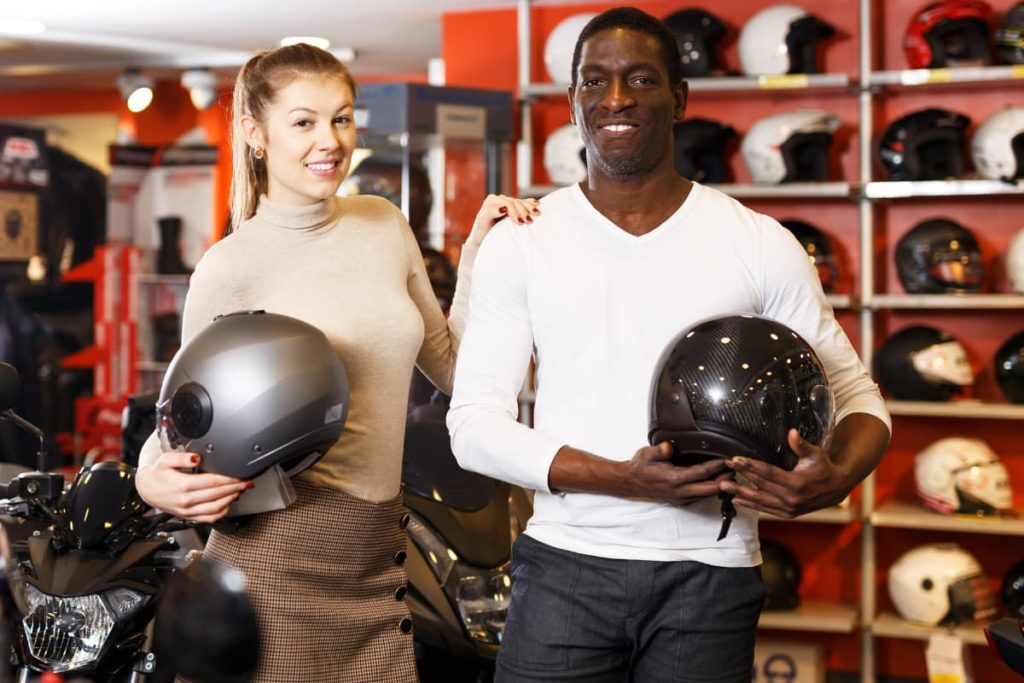 a man and woman shopping for a motorcycle helmet in a motorcycle store