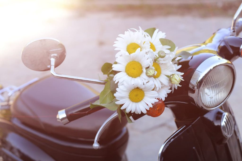 flowers on the handlebars of a vintage style black scooter