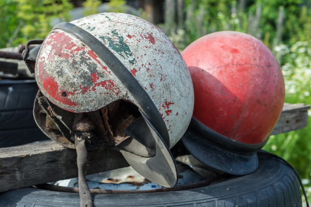 2 helmets with visible damange - cracked, peeling exteriors, worn & harden straps and interior liners