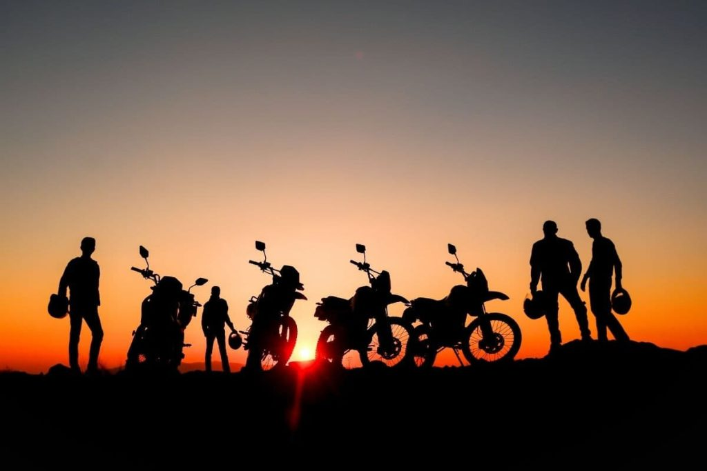 adventure bikes against a sunset with riders standing nearby with helmets