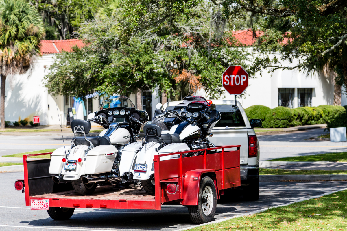 motorcycles loaded into a trailer pulled by a truck