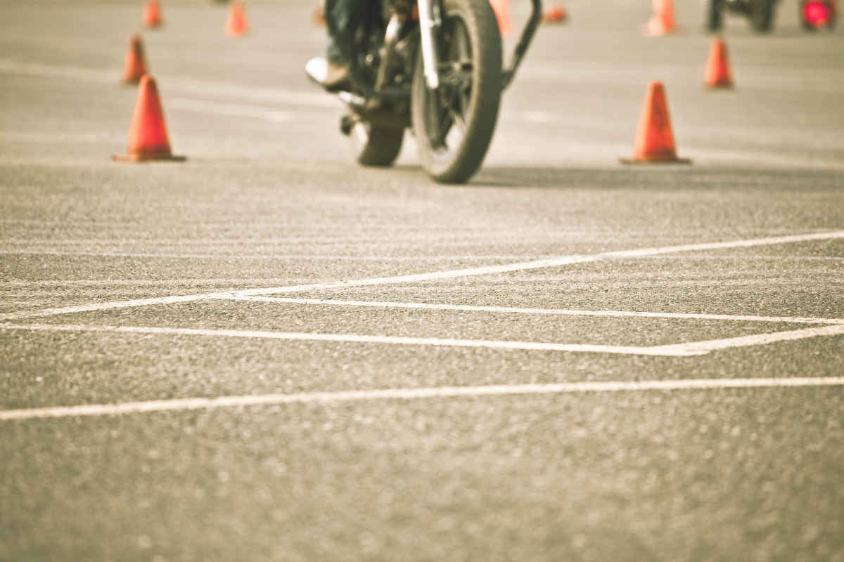 motorcycle wheels in parking lot riding with cones presumably to practice for a test